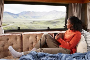 A woman sitting on a couch in an RV with a mug in her hand looking out the window.