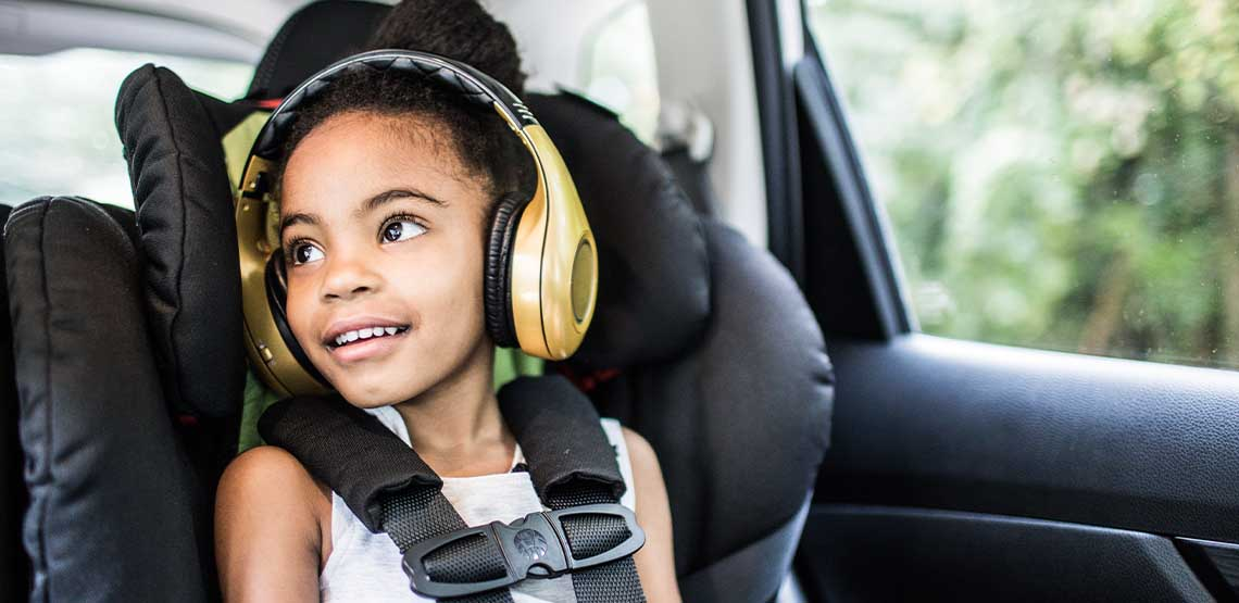 A child in a car seat wearing headphones.