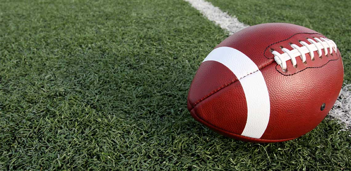 A football resting on grass.